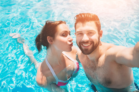 Cheerful youthful guy and lady resting while swimming pool outdoor. Couple in water. Guys do summer selfie