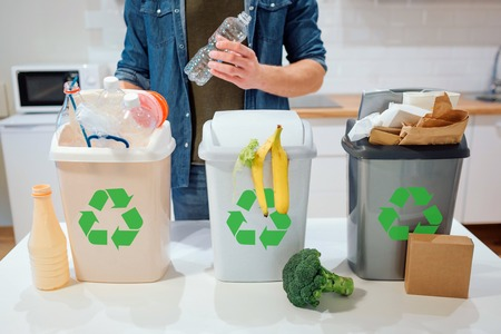 Waste sorting at home. Recycling. Man putting plastic bottle in the garbage bin in the kitchen