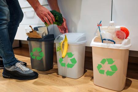 Clasificación de residuos a domicilio. Vista recortada del hombre poniendo brócoli en el cubo de la basura. Cubos de basura coloridos para clasificar los desechos en la cocina