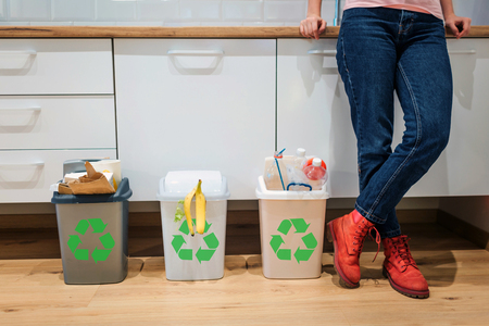Waste sorting. Cropped view of colorful garbage bins filled with plastic, bio food, paper near womans legs in the kitchen