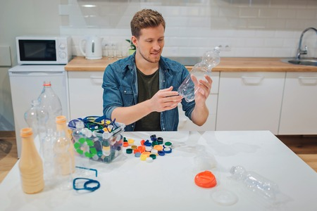 Recycling. Young smiling man is sorting empty plastic bottle and lids while sitting at the table