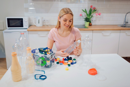 Recycling. Young smiling woman is sorting emty plastic bottle and lids while sitting at the table Imagens