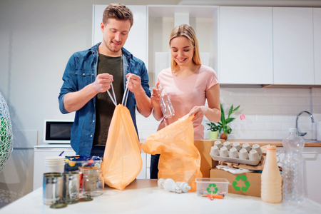 Recycling. Responsible young family putting empty plastic and paper in bags while standing near the table filled with waste at home