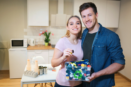 Recycling. Young smiling couple holding plastic lids in the container with green recycle icon on kitchen background
