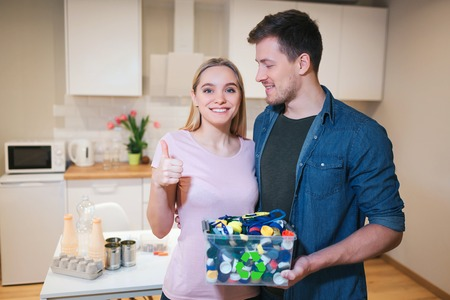 Protect the environment. Young smiling family holding recycling container filled with electronic waste on kitchen background