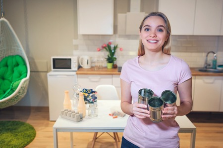 Recycling. Young smiling woman holding metal tin cans for reuse on kitchen background Foto de archivo - 118842965