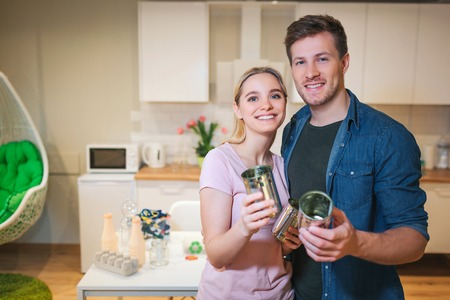 Recycling. Young smiling family holding metal tin cans for reuse on kitchen background Stock Photo