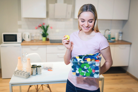 Protect the environment. Plastic lids prepared for recycling. Young smiling woman holding recycling container filled with bottles lids on kitchen background