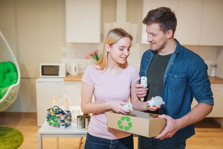 Recycling, reuse. Young smiling family putting white light bulbs into paper box with recycling symbol on kitchen background Stock Photo