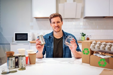 Recycling. Young smiling man is sorting empty glass bottles and metal cans while sitting at the table with other waste at home Reklamní fotografie