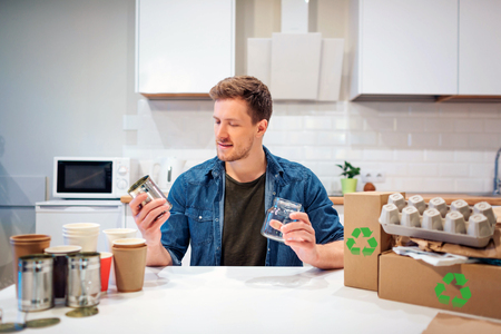 Recycling. Young smiling man is sorting metal cans and glass bottles while sitting at the table with other waste at home