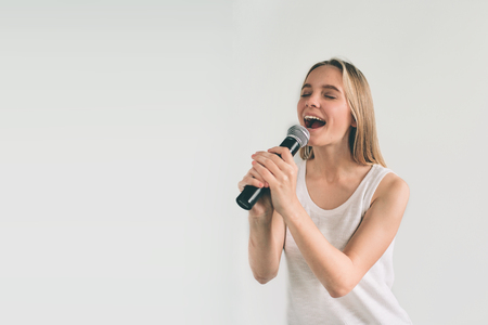Girl Rocking Out. Image of a women singing to the microphone, isolated on light. Emotional portrait of an attractive kid on a gray background. 版權商用圖片