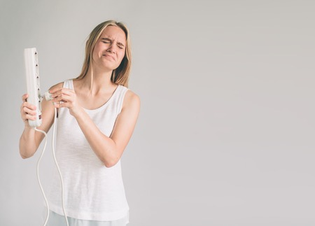 smiling happy woman using plug pull out socket showing saving electric concept isolated on wall background with lifestyle clothing