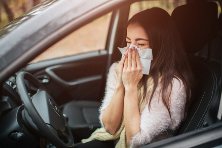 young woman with handkerchief. Sick girl has runny nose. female model makes a cure for the common cold in the car