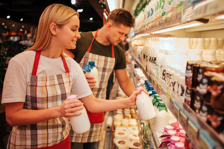 Young man and woman stand in grocery store and dairy shelf. They hold one bottle milk and take another. Young man stand behind and do same thing. Serious concnetrated workers. Stock fotó