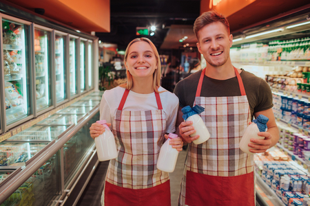 Young man and woman stand in grocery store and dairy shelf. They hold glass bottles of milk and pose on camera. Happy positive workers smile.