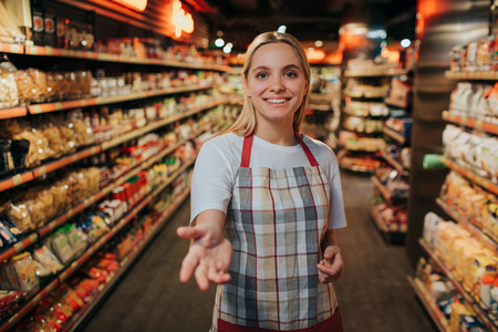 Young woman stand in line between two pasta shelfs in grocery store. She reach hand to camera and smile. Model posing.