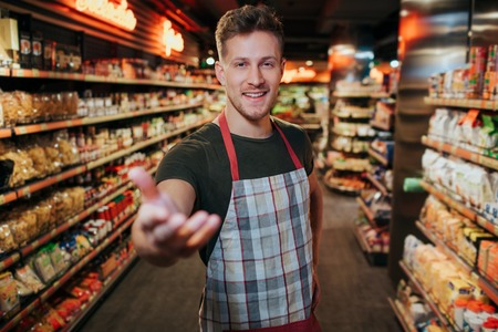 Handsome young man stand in grocery store among pasta shelfs. He reach hand to camera and smile