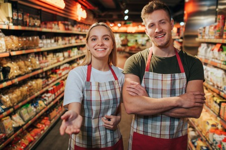 Happy cheerful young man and woman stand in grocery store among pasta shelfs. They pose on camera and smile. Young woman reach hands to camera