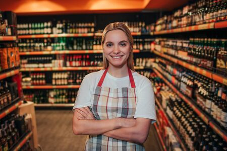 Young woman stand in grocery store among alcohol shelfs. She hold hands crossed and smile. Posing on camera. Wearing apron alone