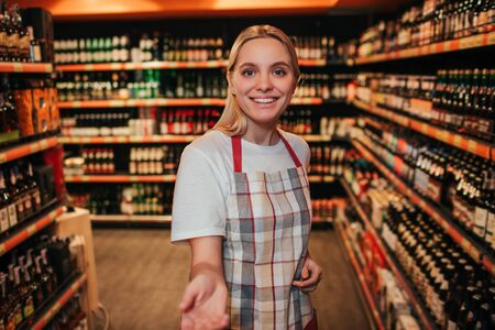 Young woman stand in alcohol shelfs in grocery store. She reaxh hand to camera and smile. Cheerful happy young woman