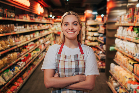 Busy young woman stand in line between shelfs with pasta. She pose on camera and smile. Happy positive model. Stok Fotoğraf