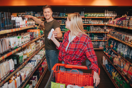 Young couple in grocery store. Woman get deodorant from man. He stant at hygiene shelfs. People look at each pther and smile. Cheerful buyers. Stok Fotoğraf