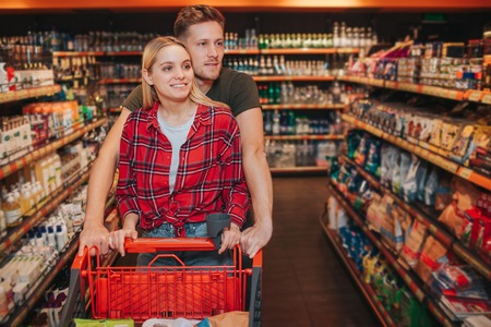 Young couple in grocery store. They walk together among shelfs with hygiene goods and look at them. People carry trolley. Cheerful happy buyers.