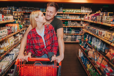 Young couple in grocery store. Lovely man and woman look at each pther and smile. They carry grocery trolley. People walk among hygiene goods shelfs. Stok Fotoğraf