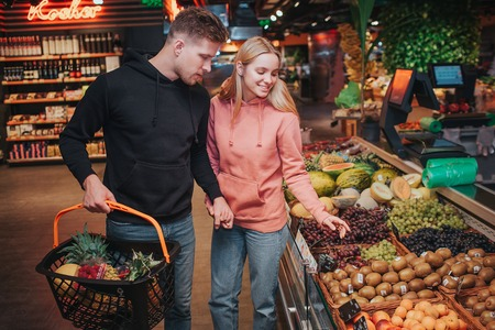 Young couple in grocery store. They pick up fruit together. Exotical and different kind of berries on shelfs.