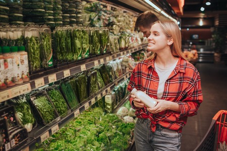 Young blonde cheerful woman in grocery store. She look at shelfs with different herbs and smile. Young woman nake a choice. Happy and positive.