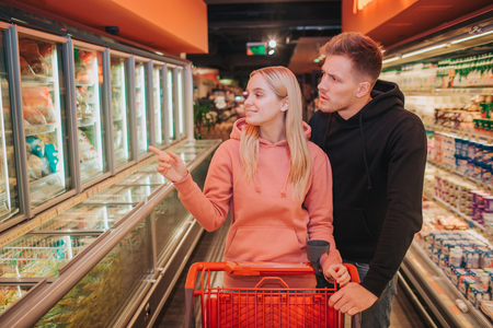 Young couple in grocery store. They carry trolley together and look to left. Woman point on dumplings. Shopping and food buying.