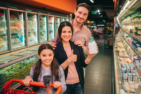 Young parents and daughter in grocery store. They stand between product shelfs and pose on camera. Girl hold trolley. Group smile. Zdjęcie Seryjne