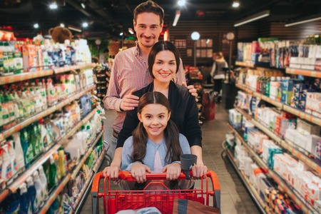 Young parents and daughter in grocery store. They walk among hygeine shelfs and smile on camera. Girl carry trolley. Man embrace woman.