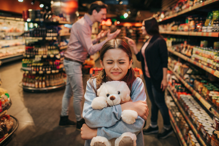 Young parents and daughter in grocery store. She sit in trolley and embrace toy bear. Girl keep eyes closed. Parents hav quarrel behind.
