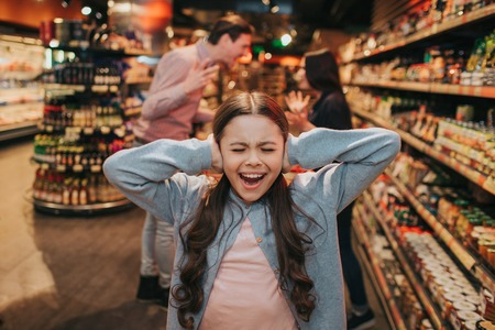 Young parents and daughter in grocery store. Girl screaming and crying. She keep ears closed. Her parents have argue and quarrel behind. Фото со стока