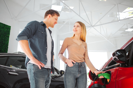 Young smiling family buying first electric car in the showroom. Woman showing to her husband how she charge modern eco-friendly vehicle with the power cable supply. Safe car for ecology