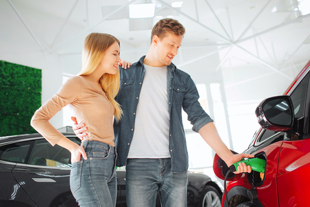 Young smiling family buying first electric car in the showroom. Man charging modern eco-friendly vehicle with the power cable supply plugged in