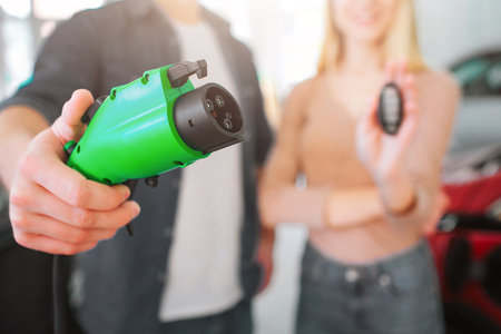 Close-up of green electric charging plug in hand, electric car concept. Woman holding car key. Young smiling family buying first electric car in the showroom. Green energy Stock Photo