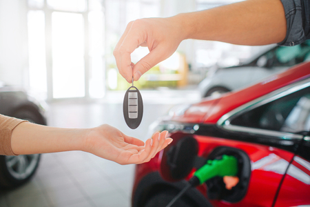 Young family buying first electric car in the showroom. Close-up of male hand giving car key to female hand on battery electric car background. Eco car sale concept