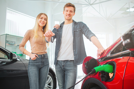 Young smiling family buying first electric car in the showroom. Attractive man holding car key while standing between his wife and eco-friendly car. Electric car sale concept