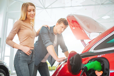 Young family buying first electric car in the showroom. Attractive couple looking at eco-friendly car battery and power cable supply. Electric car sale concept Stock Photo - 119510786