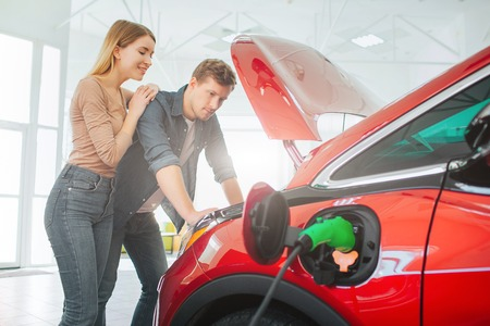 Young family buying first electric car in the showroom. Attractive couple looking under eco-friendly car hood. Electric car sale concept