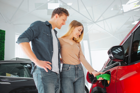 Young smiling couple buying first electric car in the showroom. Woman charging modern eco-friendly vehicle with the power cable supply plugged in Stock Photo