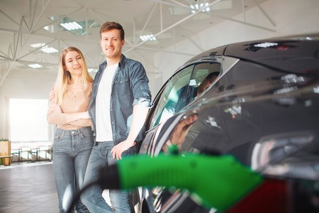 Young smiling family buying first electric car in the showroom. Environmental protection. Modern green vehicle with renewable energy