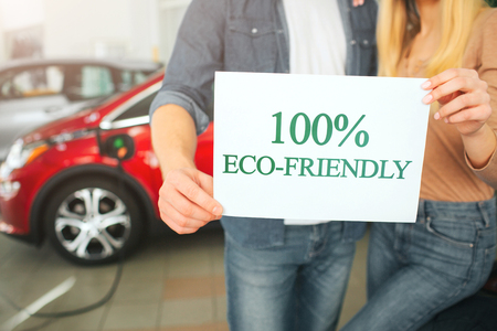 Young family buying first electric car in the showroom. Eco car. Close-up of hands holding paper with word Eco-friendly on battery electric car background. Automotive eco technology