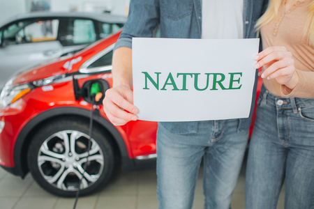 Young family buying first electric car in the showroom. Green car. Close-up of hands holding paper with word Nature on battery electric car background. Environment protection.