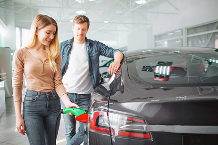 Young couple buying first electric car in the showroom. Woman charging ecological hybrid car with the power cable supply plugged in. Modern trends with renewable energy