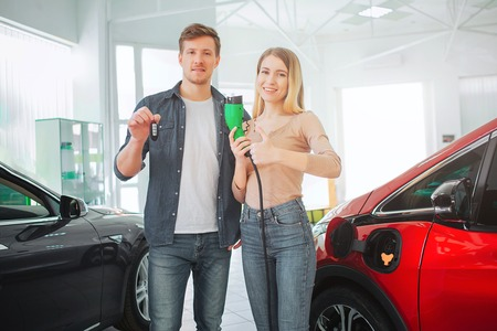 Young smiling family buying first electric car in the showroom. Environmental protection. Attractive man and woman holding car key and electric car charging plug. Green electric car sale concept