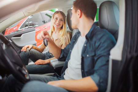 Young family buying first electric car in the showroom. Attractive smiling couple talking and sitting in the cabin of modern electric hybrid vehicle before test driving. Electric car sale concept Stock Photo